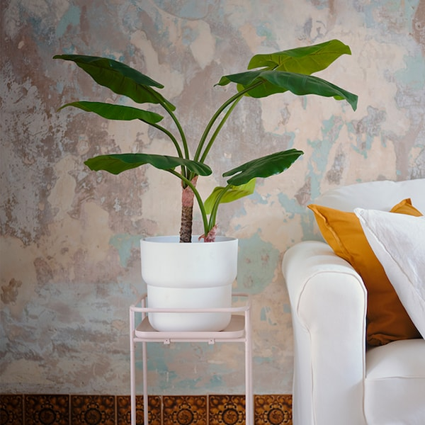 A white plant pot with a tropical plant on top of a light pink plant pot stand.