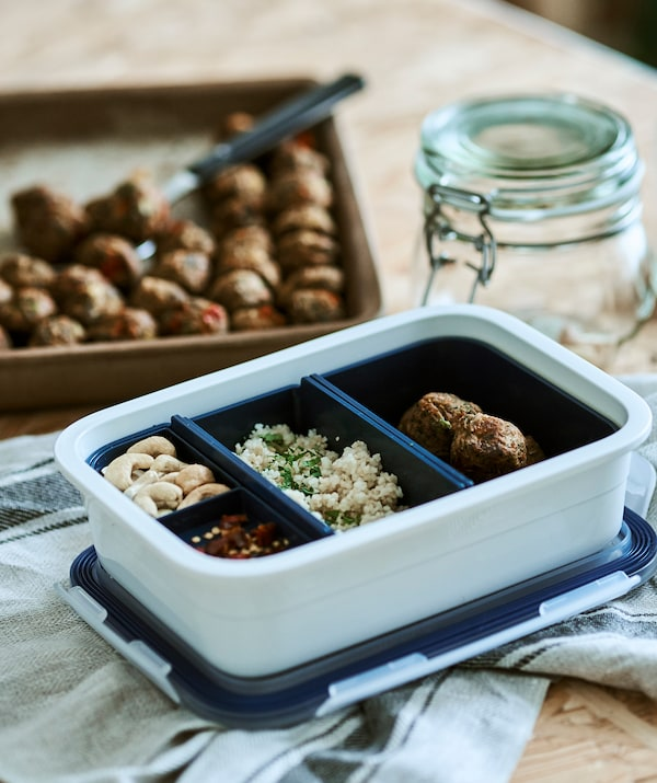 A white plastic food tub with blue inserts, each contains different food, on a linen tea towel beside a tray of veggie balls.