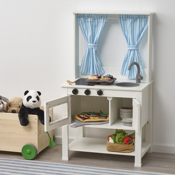 A white play kitchen for children, with several other toys.