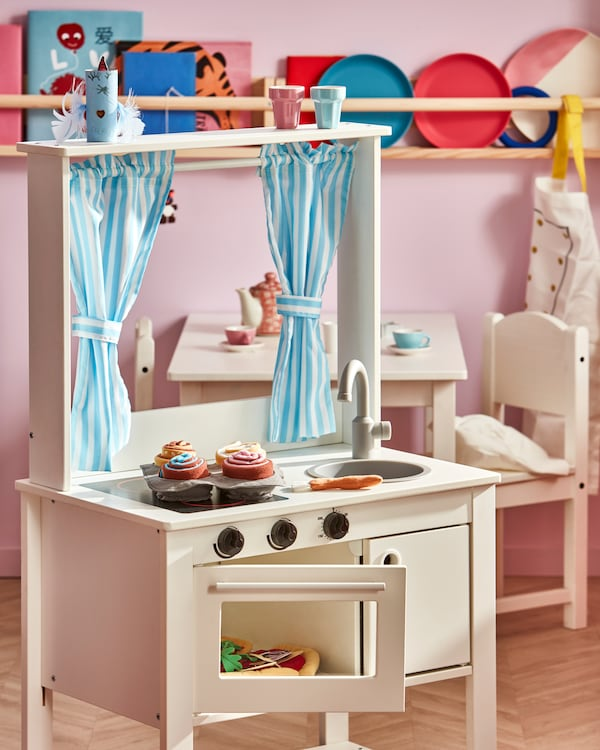 A white play kitchen with an open oven door and a 6-piece roll set with 4 colourful buns, 1 bread brush and 1 baking tray.