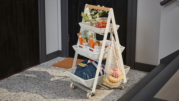 A white RISATORP steel cart with three levels and a wooden handle, filled with a complete breakfast for two.