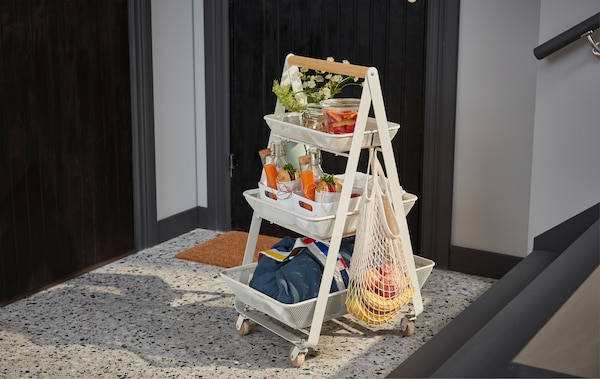 A white RISATORP steel trolley with three levels and a wooden handle, filled with a complete breakfast for two.