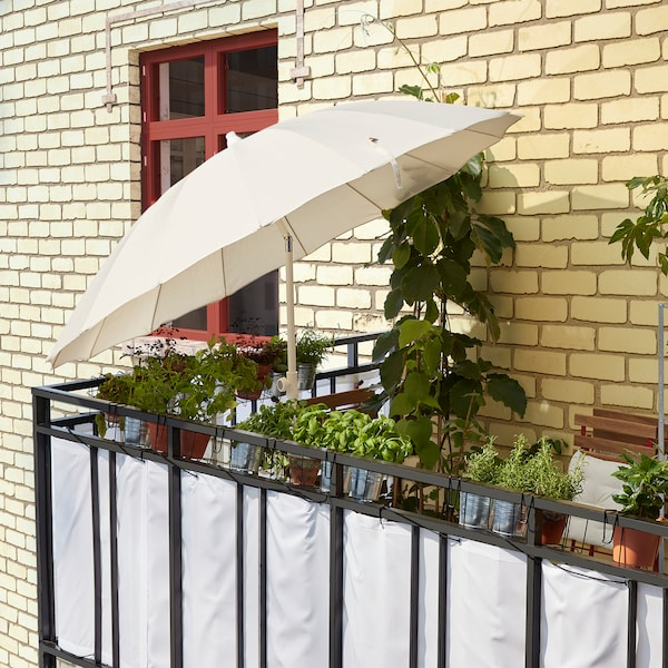 A white SAMSÖ/GRYTÖ parasol is tilted to block sunlight and provide shade on a balcony.