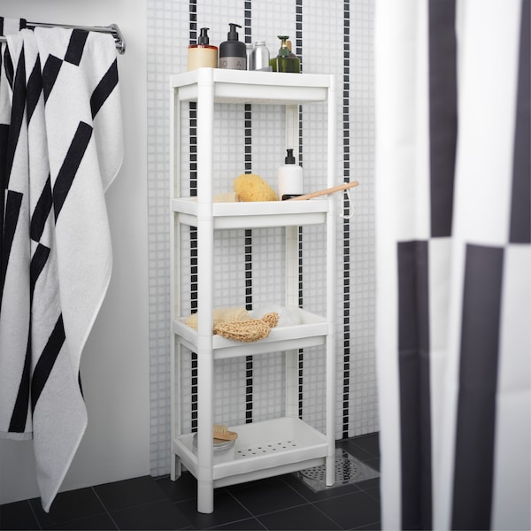 A white shelf unit is standing in a black/white shower and is storing shower necessities like shampoos and more.
