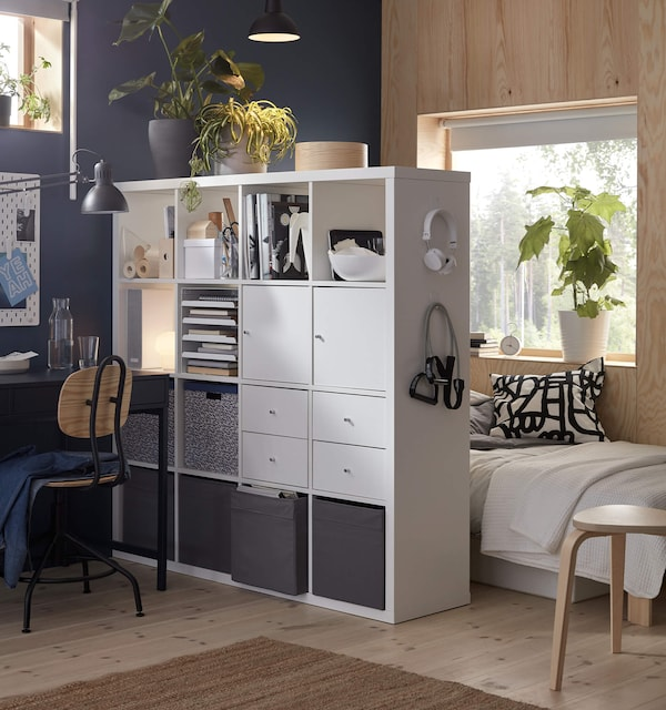 A white shelving unit holding various items and used to divide a small space into study and sleeping areas
