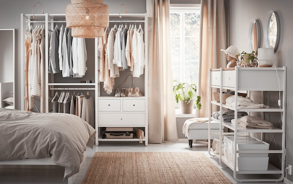 A white shelving unit in a bedroom, with drawers and hanging clothes rails holding shirts and other hanging garments.