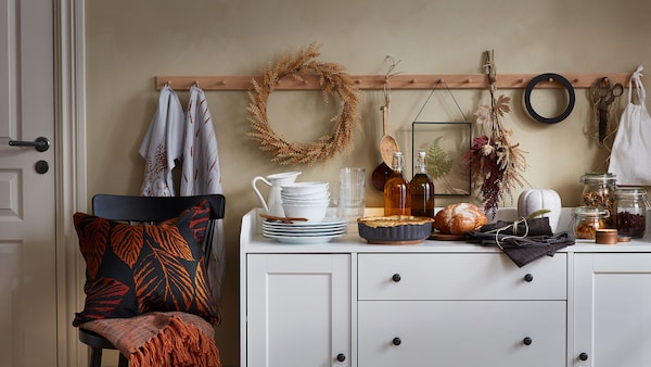 A white sideboard with modern rustic décor including a pie dish, a round loaf of bread, white crockery, and a wooden rail on the wall behind, decorated with a wreath.