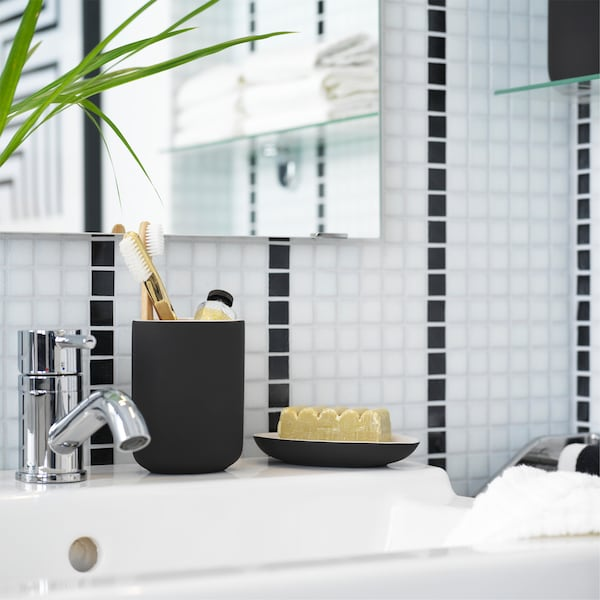 A white sink cabinet where toothbrushes stand in a dark grey toothbrush holder in a black/white bathroom.