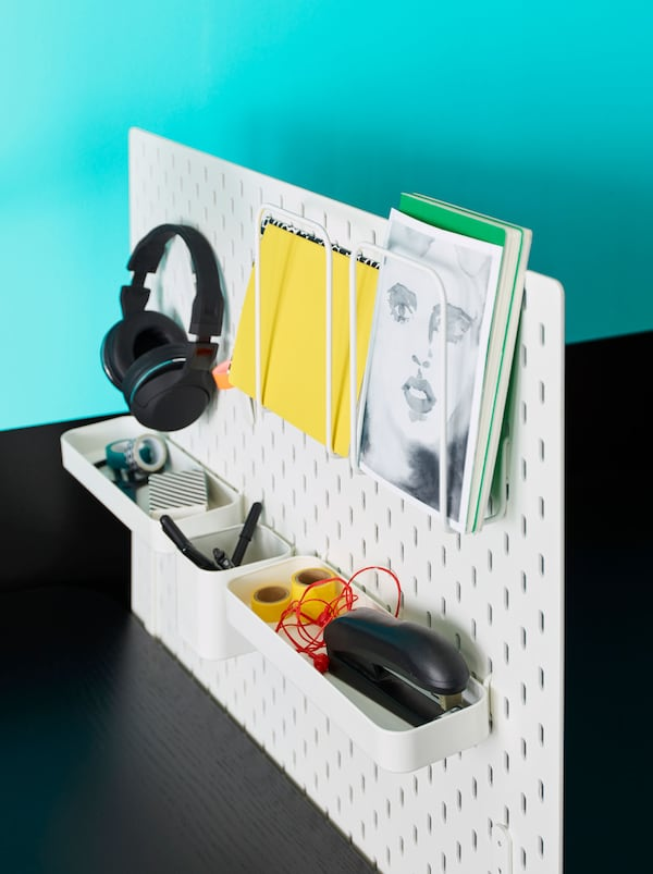 A white SKÅDIS pegboard combination with tray containing stationery, headphones on a hook, and letter holders with documents.