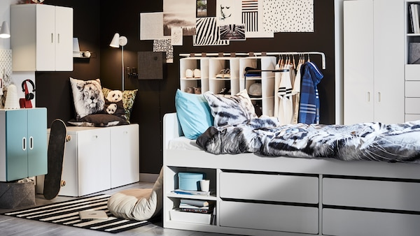 A white SLÄKT bed with storage and URSKOG bed linen with a tiger pattern stands in the middle of a child's bedroom.