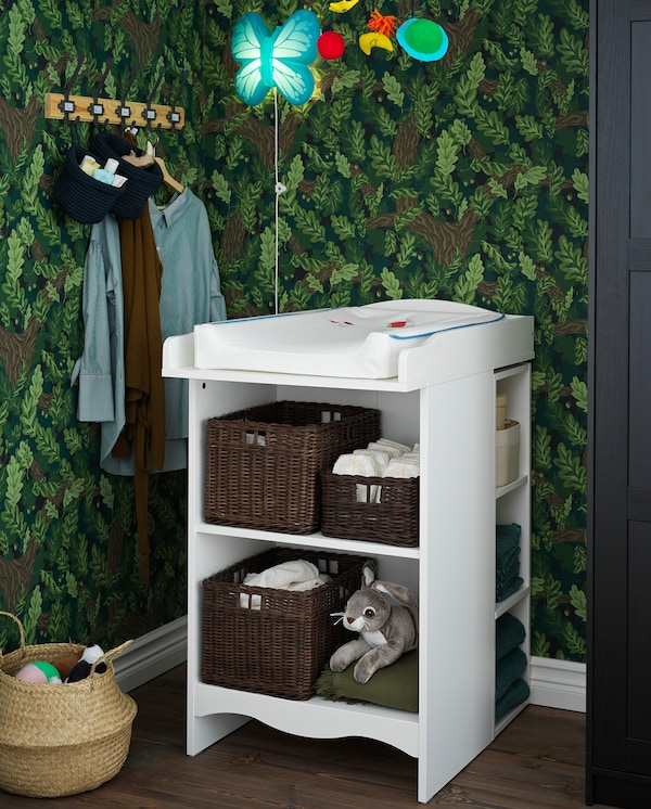 A white SMÅGÖRA changing table with many shelves with a toy, baskets, diapers and more.