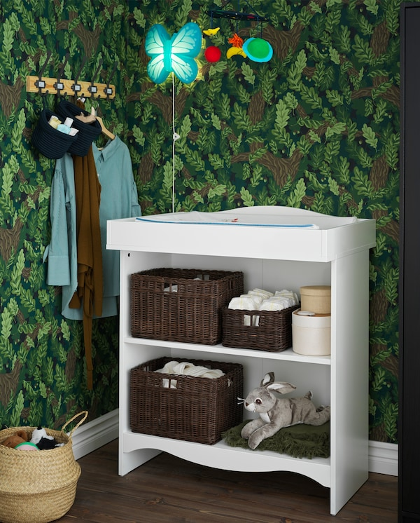 A white SMÅGÖRA changing table with two spacious shelves with towels, baskets and toys.