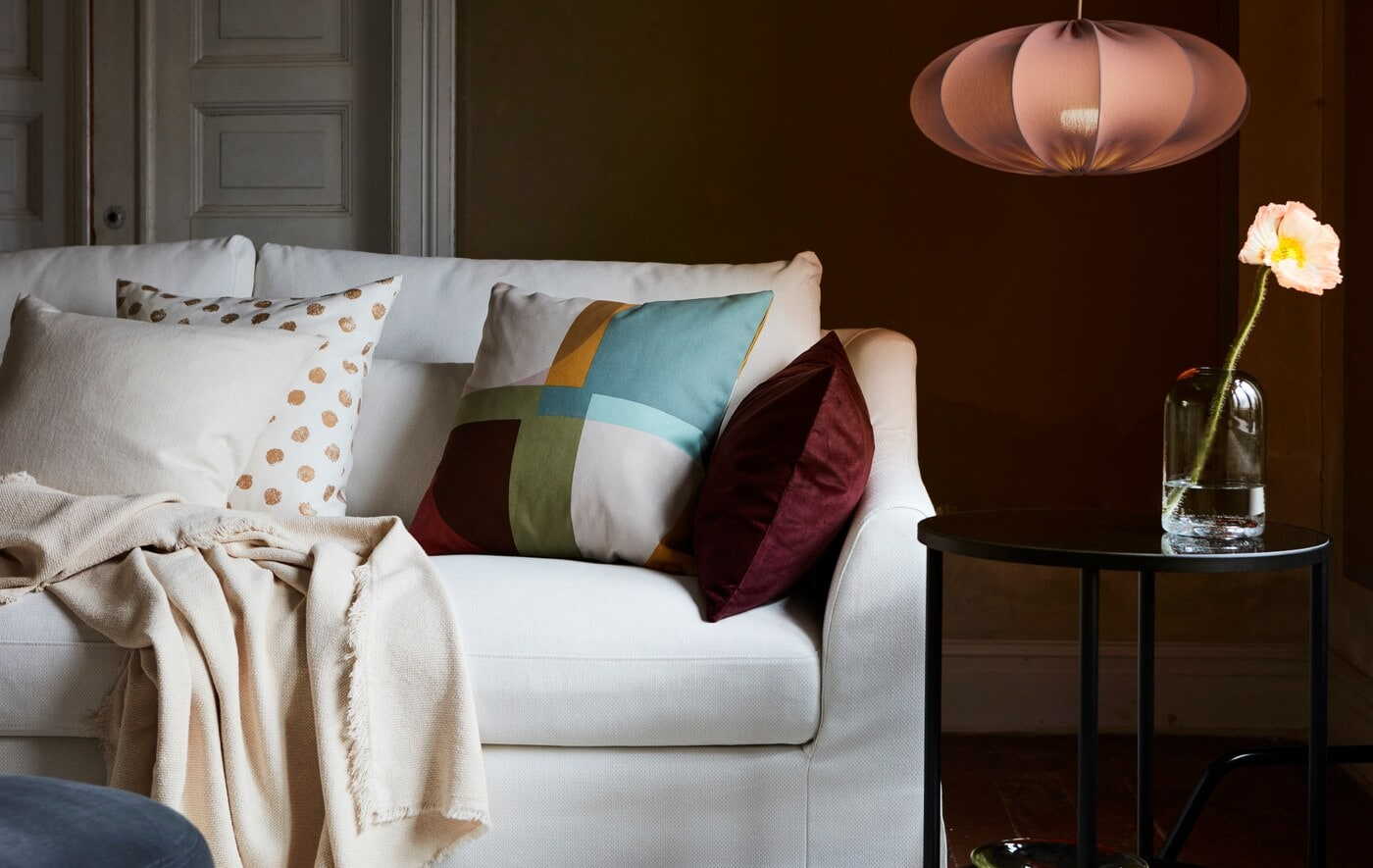 A white sofa in a living room with a mix of cushions and a throw. Next to it is a black side table and REGNSKUR lamp.