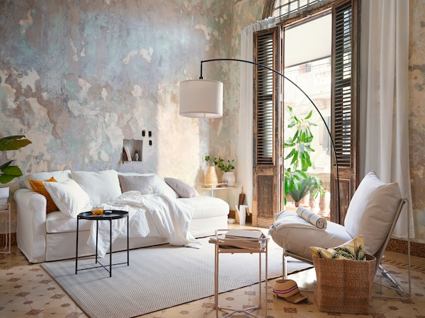 A white sofa placed in a beige-grey setting with scatter cushions, a black side table, and a white occasional chair.