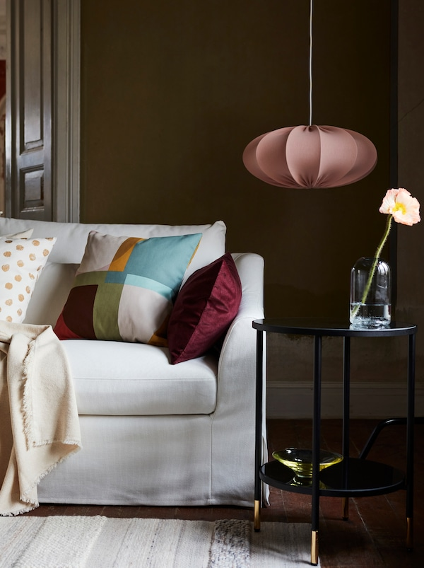 A white sofa with a variety of patterned sofa cushions. Beside it is a black side table with vase as well as a hanging lamp.