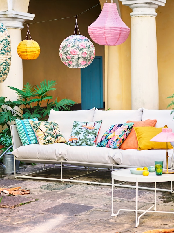 A white sofa with various coloured and patterned scatter cushions placed outside with a variety of hanging lanterns.