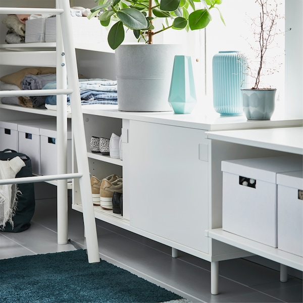 A white storage bench is placed by a loft bed ladder, and one of the opened sliding doors shows shoes stored inside.