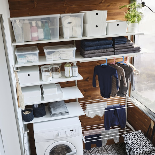 A white storage system with many shelves, two drying racks and a clothes rail where children's clothes hang to dry.
