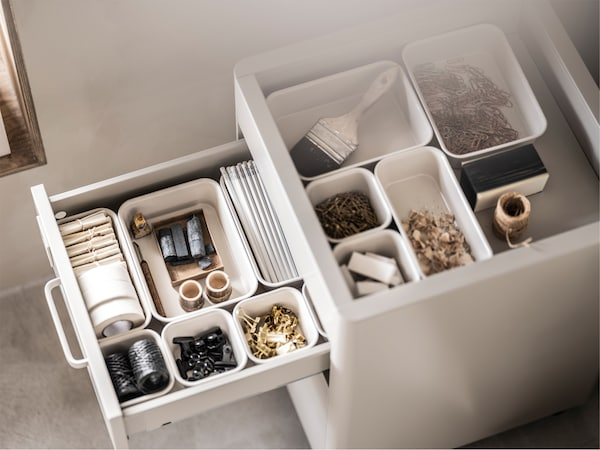 A white storage unit with an open drawer and open top filled with different sized beige NOJIG boxes holding small objects.