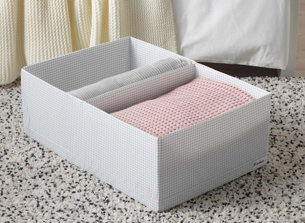 A white STUK storage box with pink and white linens folded inside of it