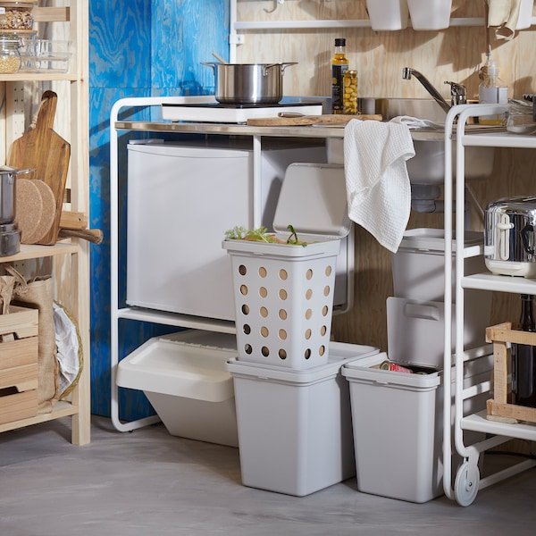 A white SUNNERSTA mini-kitchen, a storage system in pine and light grey waste sorting bins in different sizes and shapes.