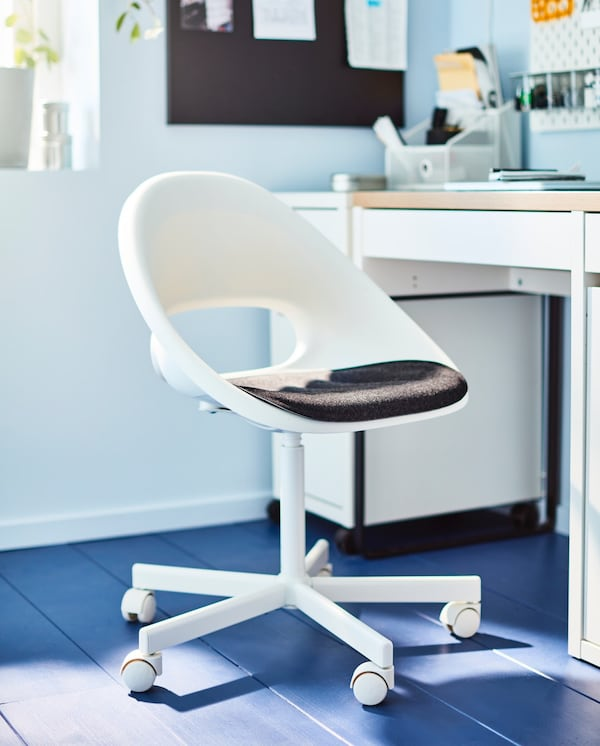 A white swivel chair which has black seat. In background we can see memo board, desk organiser and a white table