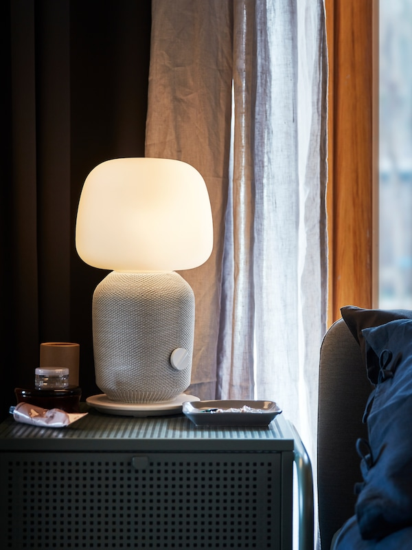 A white SYMFONISK lamp and WiFi speaker stands on a green bedside table/cabinet, its lamp lit in the dark room.