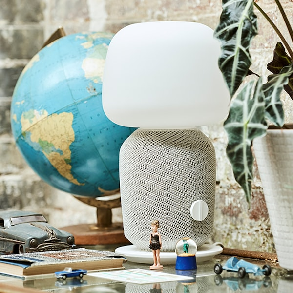 A white SYMFONISK lamp speaker with a globe in the background.