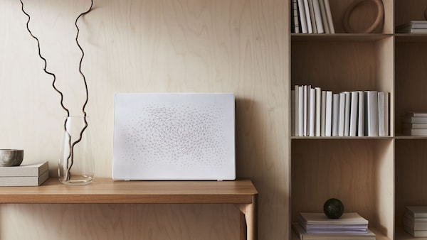 A white SYMFONISK picture frame with WiFi speaker is displayed on a table with a vase alongside a bookshelf.