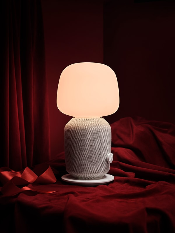 A white SYMFONISK speaker light with red ribbon sitting below