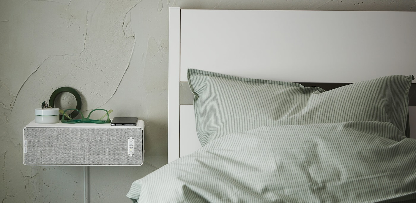 A white SYMFONISK Wi-Fi speaker shelf mounted to the wall next to a bed