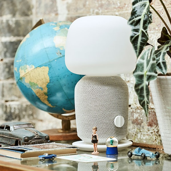 A white SYMFONISK WiFi lamp speaker on a side table, next to a globe.