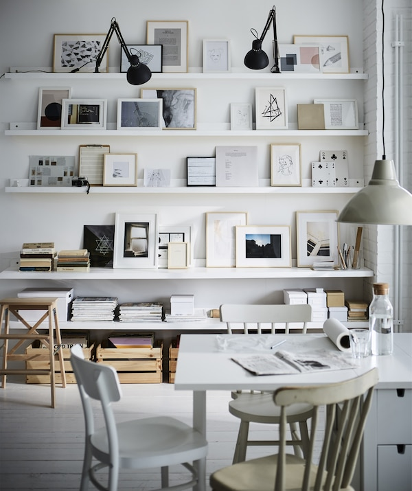 A white table in front of a display of paintings on white picture ledges and shelves.