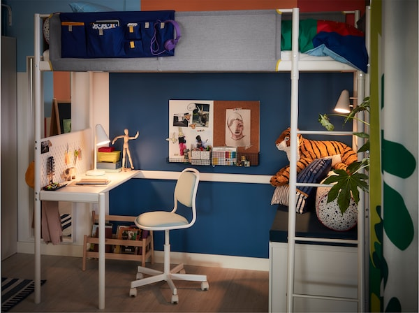 A white table lamp brightens up a desktop and a blue children's desk chair under a loft bed.