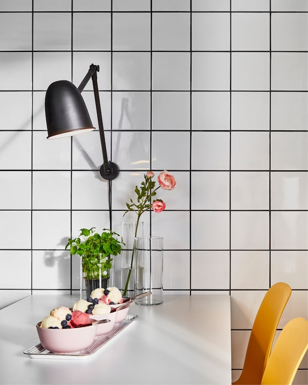 A white table, yellow chairs and a black wall lamp that's mounted on a white tile wall. Ice cream in pink bowls on the table.