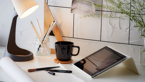 A white tablet stand with a tablet, placed on a desk with a lamp, a mug, and some pens.