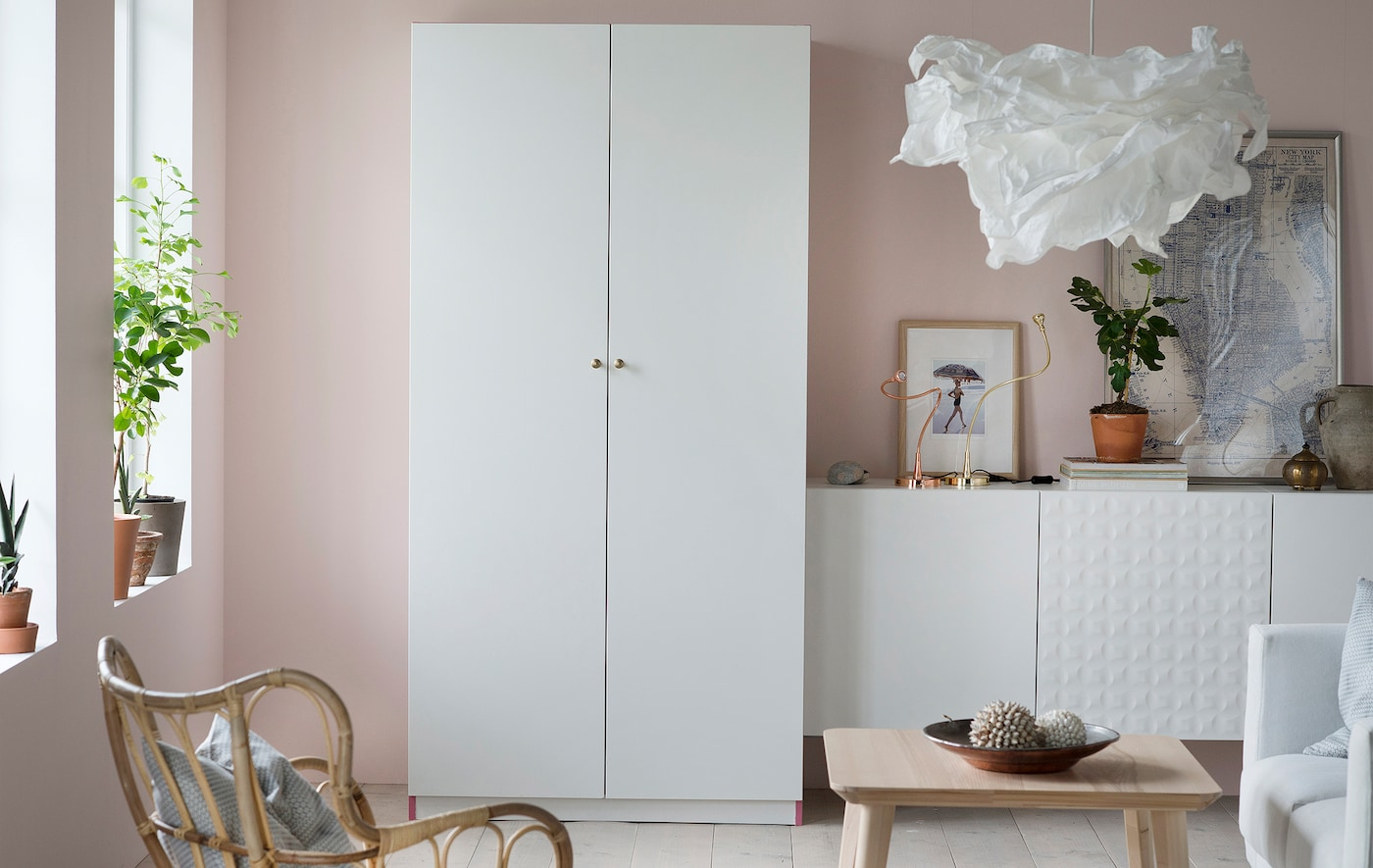 A white tanem PAX wardrobe in an airy living room area, with its two white doors closed so the room feels calm and inviting.