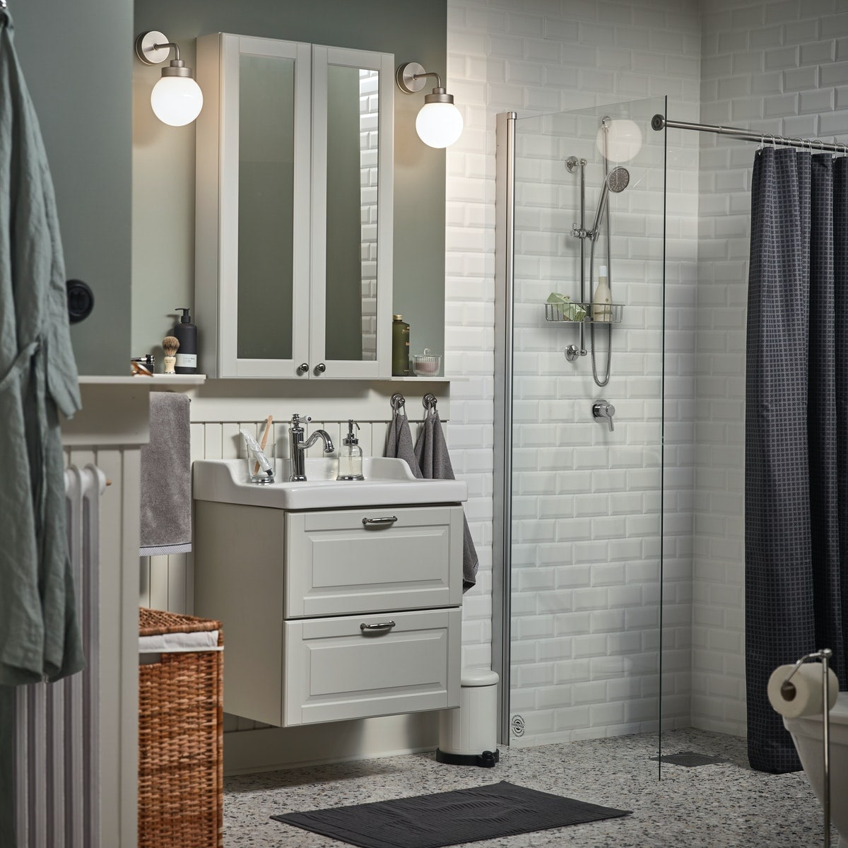 A white-tiled bathroom with light green walls, two FRIHULT wall lamps on either side of a GODMORGON mirror cabinet.