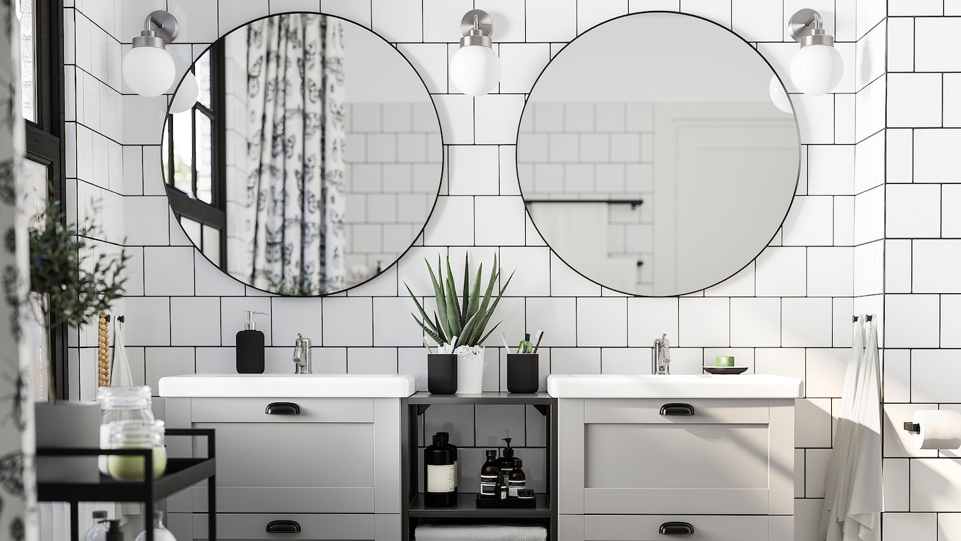A white-tiled bathroom with two round mirrors, two washbasins in grey and white, a black trolley and three wall lamps.