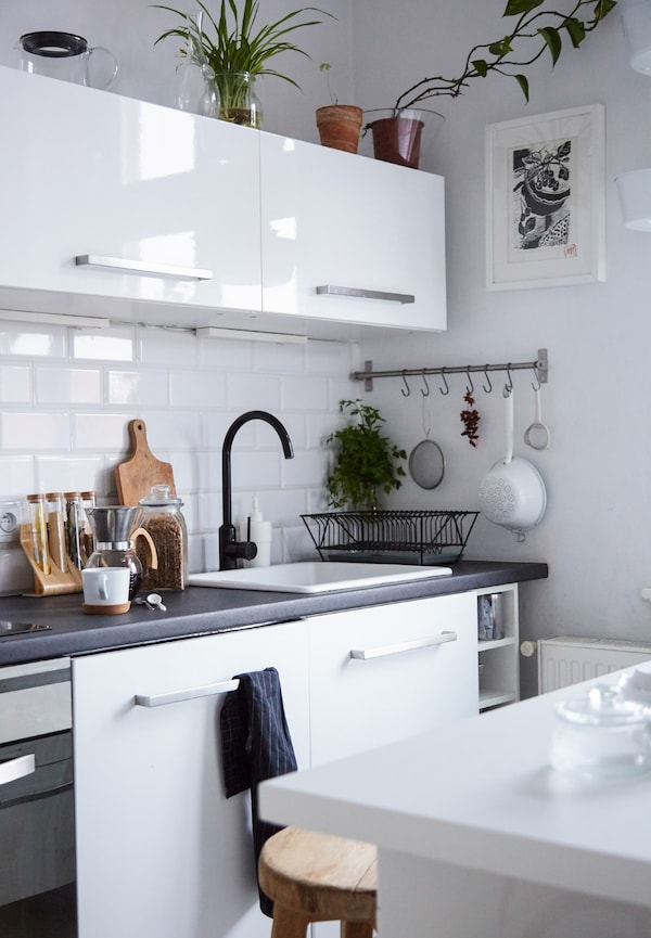 A white tiled kitchen with kitchen island and high-gloss white cabinets.