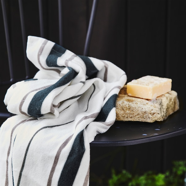 A white towel with blue and grey stripes on a black chair with a bar of soap on a stone.