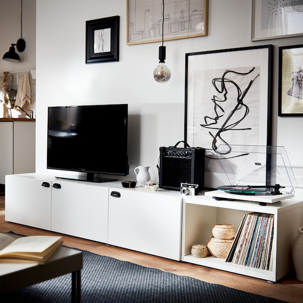A white TV bench with black handles, a black TV, a black speaker, a grey rug and framed posters in different sizes.