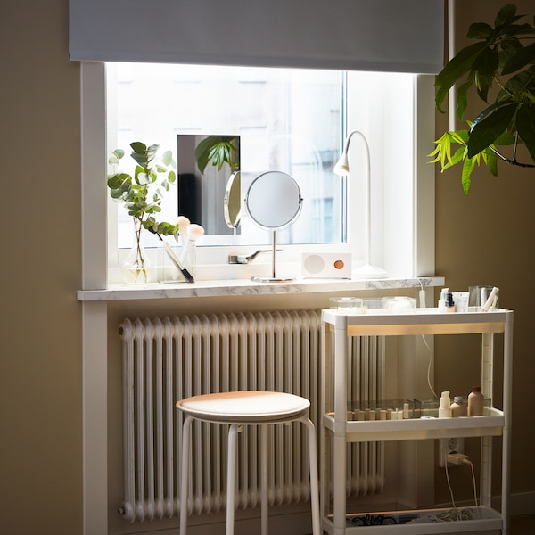 A white VESKEN trolley and a white MARIUS stool stand in front of a window with different objects on the windowsill.