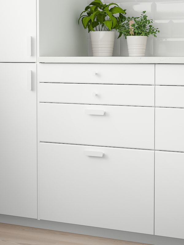 A white wall cabinet with two doors, a white worktop with two green plants on top and four white drawers below.