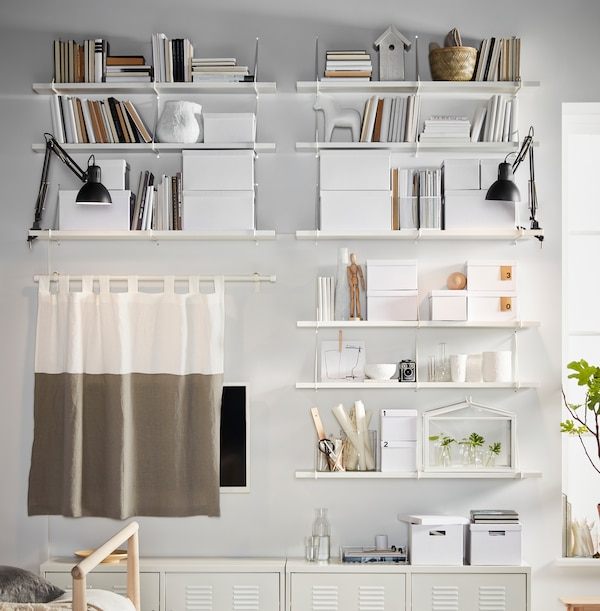 A white wall filled with shelves, TJENA storage boxes and IKEA PS cabinets, all white and placed in a symmetrical way.