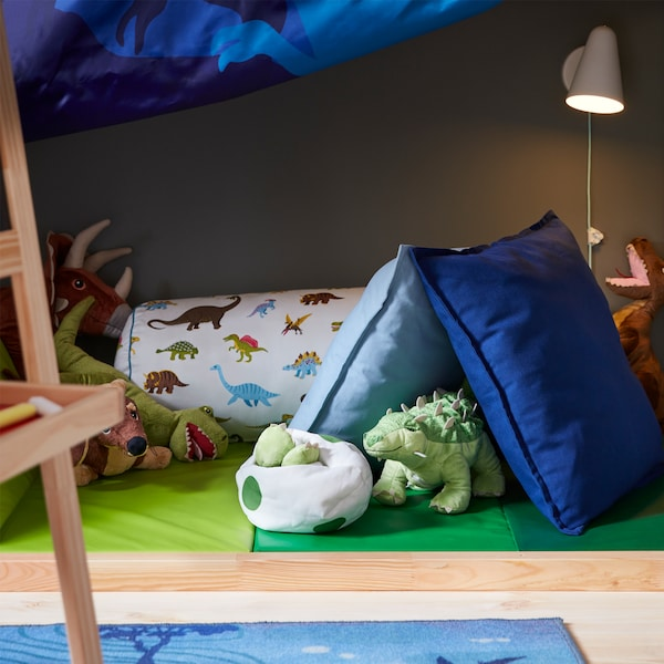 A white wall lamp that's lit and a green folding gym mat with dinosaur soft toys and blue/dinosaur-patterned cushions.