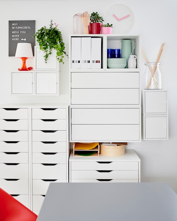 A white wall-mounted cabinet combination and white drawer units with dinnerware, decorative items and magazine files.
