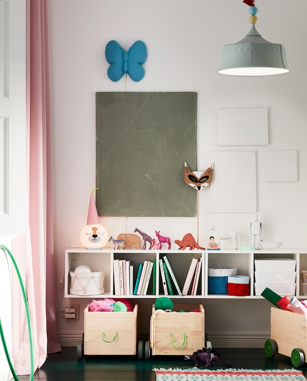 A white, wall-mounted shelf unit. Toys, books, baskets and a table lamp stand on the shelves and the top surface.