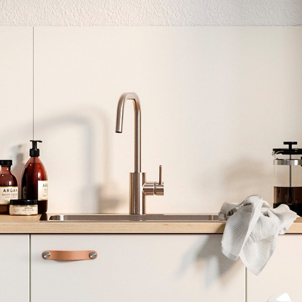 A white wall panel, a white kitchen front with leather handles under a sink, a French press and apothecary-inspired soap.