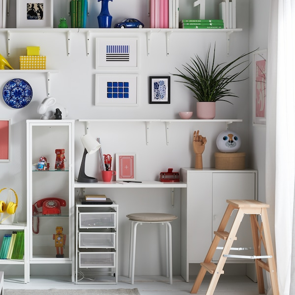 A white wall with white shelving on it holding brightly coloured books and objects, with a desk area and a round stool below.